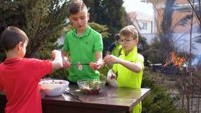 Três irmãos preparam o assado no jardim video estoque