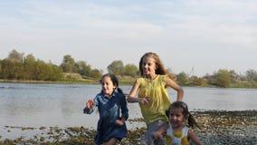 Três irmãs bonitos que correm pelo rio video estoque