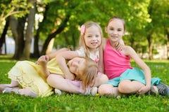 Três irmãs mais nova bonitos que têm o divertimento junto na grama em um dia de verão ensolarado Crianças engraçadas que penduram Fotografia de Stock Royalty Free