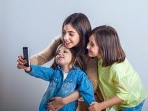 Três irmãs que levantam e que tomam selfies no estúdio fotos de stock royalty free