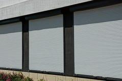 Três janelas cobertas com os obturadores plásticos brancos na parede da casa foto de stock