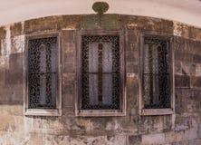 Três janelas com estrutura ornamented do metal em uma construção de pedra fotos de stock royalty free
