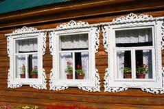 Três janelas de uma casa de madeira do condado decorada pelos quadros brancos Imagens de Stock