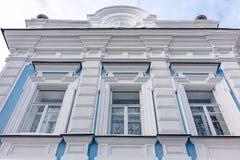 Três janelas de uma mansão velha do século XIX com as paredes azuis e brancas com distorção da perspectiva do espaço fotos de stock