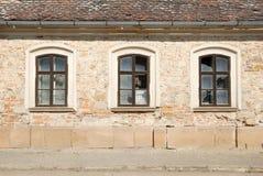 Três janelas quebradas em uma parede de uma construção danificada Fotografia de Stock Royalty Free