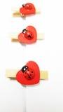 Três joaninhas de madeira em grampos da forma do coração Fotos de Stock