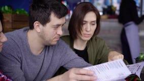 Três jovens atrativos em um café ou em um restaurante escolhem um menu das bebidas e do alimento Os amigos no dia livre vieram a vídeos de arquivo