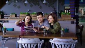 Três jovens atrativos em um café ou em um restaurante escolhem um menu das bebidas e do alimento Os amigos no dia livre vieram a video estoque