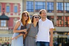 Três jovens estão no quadrado da cidade antiga Fotos de Stock