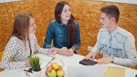 Três jovens estão trabalhando no projeto do negócio em um escritório Discussão quente video estoque