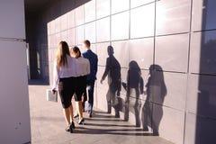 Três jovens, estudantes, duas meninas e indivíduo, vão para trás a vieram Foto de Stock Royalty Free