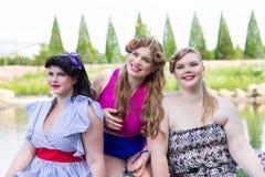 Três jovens mais o assento modelo do tamanho pelo lago Imagem de Stock Royalty Free