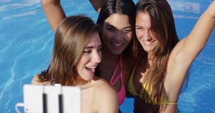 Três jovens mulheres bonitas que levantam para um selfie filme