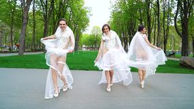 Três jovens mulheres em equipamentos 'sexy' e em véus nupciais dançam no parque da cidade video estoque