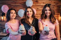 Três jovens mulheres estão e olham na câmera Eles dmile Os povos guardam três bolos nas mãos Mostram-no na câmera Ele fotografia de stock royalty free