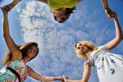 Três jovens mulheres no círculo Fotos de Stock