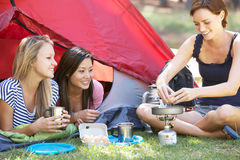 Três jovens mulheres que cozinham no fogão de acampamento fora da barraca Imagem de Stock Royalty Free