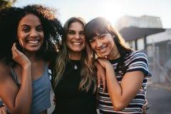 Três jovens mulheres que têm o divertimento na rua da cidade fotos de stock