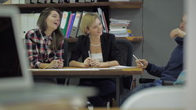 Três jovens que riem e que discutem algo que senta-se em uma mesa no escritório