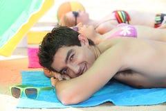 Três jovens que sunbathing Imagens de Stock