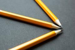 Três lápis amarelos em um fundo preto, conceito fotos de stock royalty free