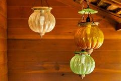 Três lâmpadas de suspensão do vintage asiático com fundo de madeira da parede fotografia de stock