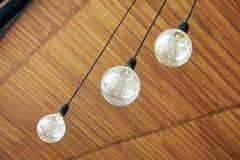 Três lâmpadas retros que penduram do teto Imagens de Stock