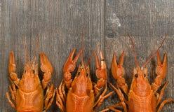 Três lagostas vermelhas em seguido no close-up de madeira velho da tabela Fotos de Stock Royalty Free