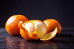 três laranjas em uma tabela de madeira preta Imagens de Stock