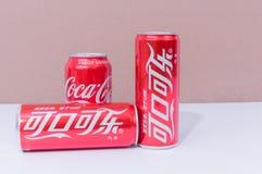 Três latas de Coca-Cola com os dois escritos no chinês foto de stock