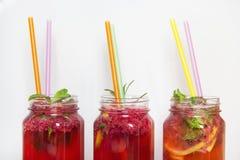 Três limonadas da framboesa e da morango com palhas no vidro Fotografia de Stock