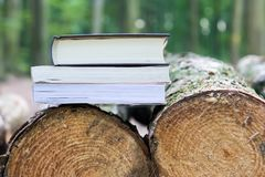 Três livros que encontram-se em árvores abatidas, salvar as árvores - eBook lido imagem de stock