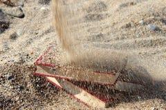 Três livros vermelhos na areia, coberta com a areia, conceito do transience do tempo, borraram o fundo Fotografia de Stock