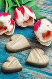 Três mão-cinzelaram o coração de madeira com tulipas do ramalhete Fotos de Stock Royalty Free