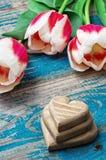Três mão-cinzelaram o coração de madeira com tulipas do ramalhete Imagens de Stock