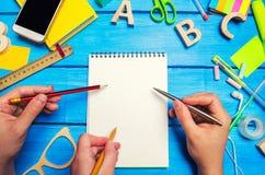 Três mãos com lápis e ponto de penas a um caderno com white pages no fundo de madeira azul do desktop Desordem criativa imagens de stock royalty free