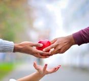 Três mãos que sustentam uma maçã vermelha Imagens de Stock