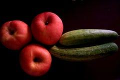 Três maçãs, dois pepinos no tiro fotografia de stock