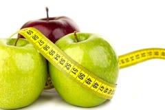 Três maçãs e fitas métricas suculentas maduras Imagens de Stock Royalty Free