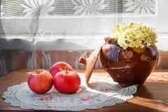 Três maçãs e potenciômetro de argila rachado com a flor na luz solar Fotografia de Stock Royalty Free