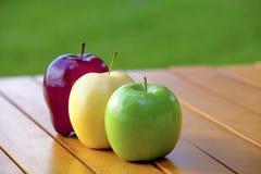 Três maçãs em um amarelo vermelho da tabela e verde fotografia de stock