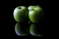 Três maçãs maduras frescas verdes no fundo preto com reflexão do lado Fotografia de Stock