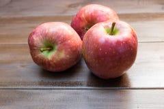 Três maçãs na tabela de madeira Foto de Stock