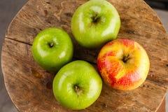 Três maçãs verdes e um vermelho Fotografia de Stock Royalty Free