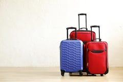 Três malas de viagem do tamanho diferente, da matéria têxtil grande & pequena, vermelha e da bagagem dura azul do shell com o pun fotos de stock royalty free