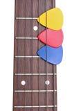 Três mediadores coloridos em um fretboard da guitarra Fotos de Stock Royalty Free