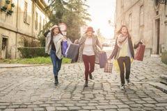 Três melhores amigos que correm na rua Fêmeas novas o melhor franco Fotos de Stock