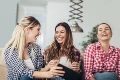 Três melhores amigos que usam a tabuleta digital junto imagem de stock royalty free