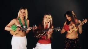 Três meninas alegres atrativas nos vestidos havaianos que jogam a guitarra da uquelele video estoque
