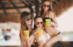 Três meninas bonitas em uma barra na praia Fotos de Stock Royalty Free